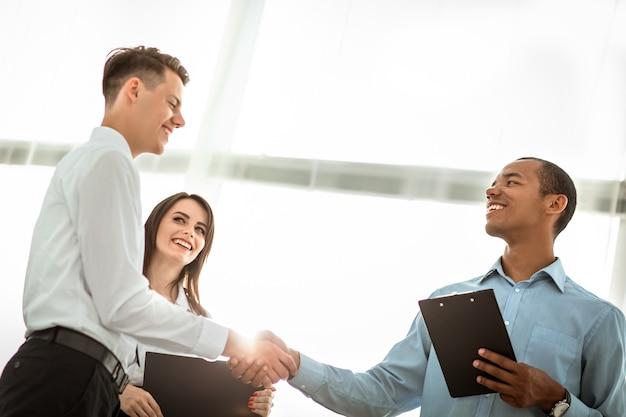 Gente de negocios amistosa dándose la mano sobre fondo borroso