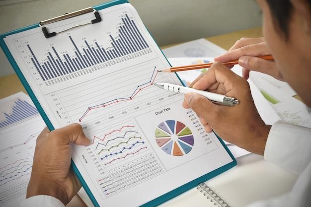 La gente de negocios analiza gráficos y cuadros financieros en el escritorio.