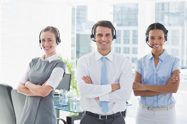 Gente de negocios con auriculares sonriendo a la cámara
