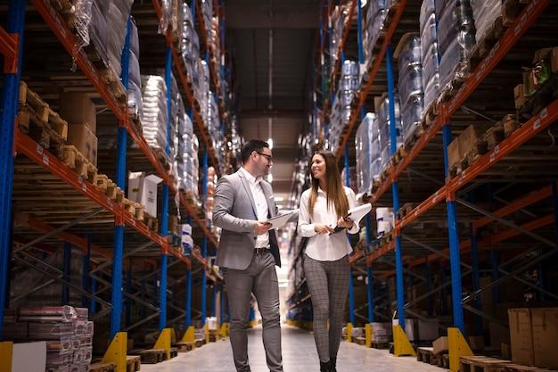 Gente de negocios caminando por un gran centro de distribución y hablando de aumentar la producción y la organización