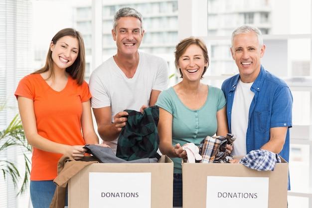 Gente de negocios casual sonriente clasificando cajas de donación