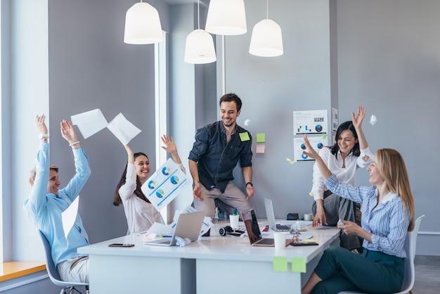 Gente de negocios celebrando y divirtiéndose en la oficina.