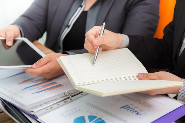 Gente de negocios comparando resultados en una tablet y una libreta