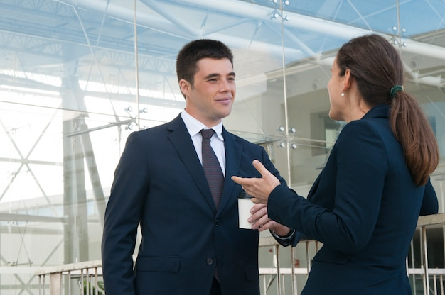 Gente de negocios contenta gesticulando y charlando al aire libre