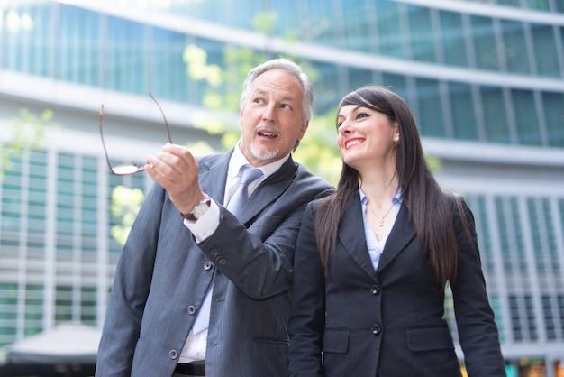 Gente de negocios conversando frente a su oficina