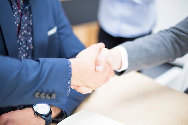 Gente de negocios dándose la mano al terminar una reunión