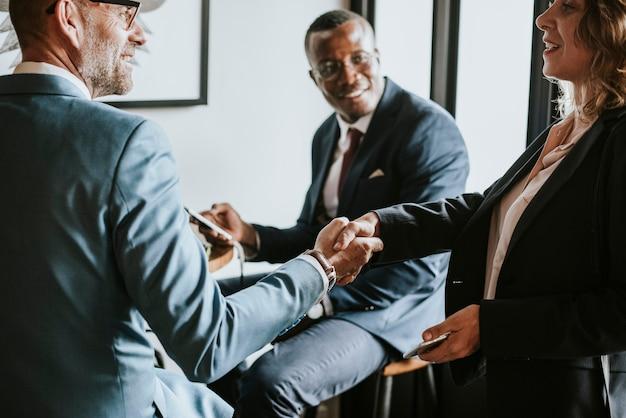 La gente de negocios dándose la mano en un café