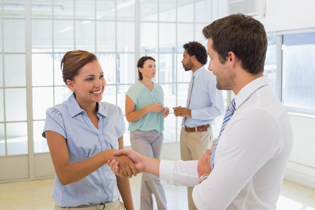 Gente de negocios dándose la mano con colegas en la oficina
