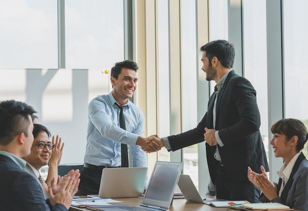 Gente de negocios dándose la mano enhorabuena al éxito laboral.