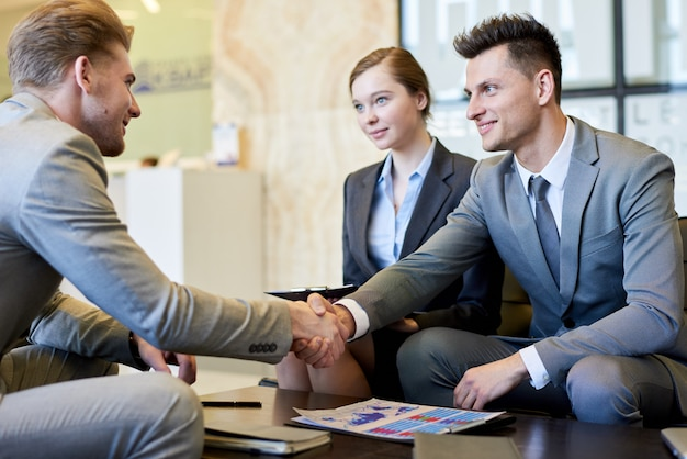Gente de negocios dándose la mano en la mesa de reunión