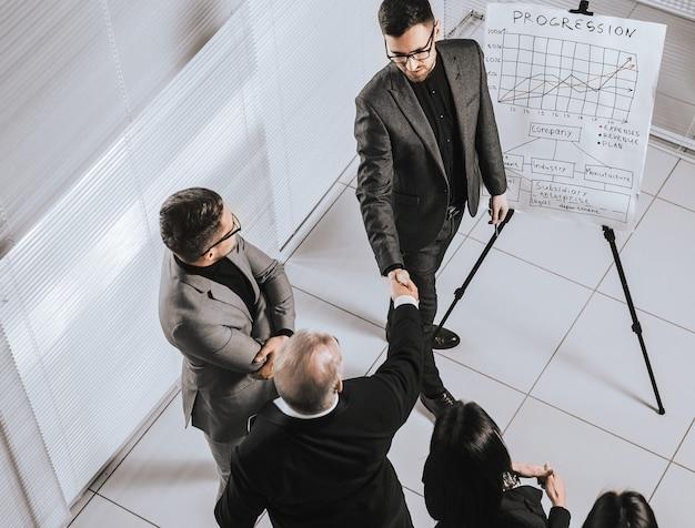 Gente de negocios dándose la mano en una reunión de oficina. días laborables de oficina
