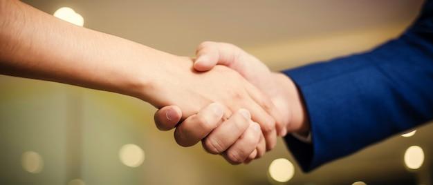Gente de negocios dándose la mano, entre reuniones en la sala de seminarios