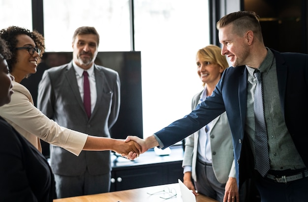 Gente de negocios dándose la mano en una sala de reuniones