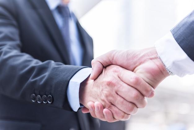 Gente de negocios dándose la mano, saludo deal concept, fondo moderno de la ciudad.