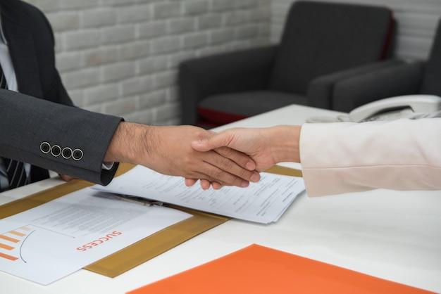 Gente de negocios dándose la mano sobre el escritorio.