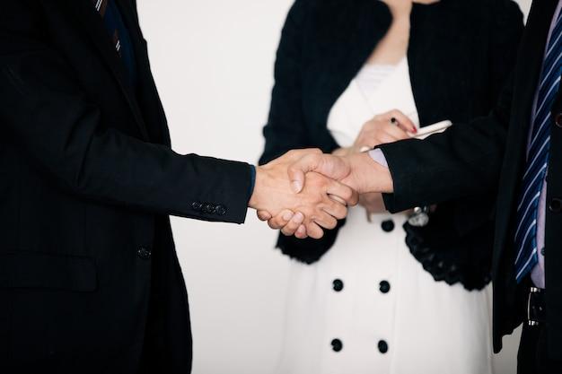 Gente de negocios dándose la mano y sonriendo su acuerdo para firmar un contrato y terminar una reunión