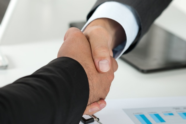 Gente de negocios dándose la mano, terminando una reunión
