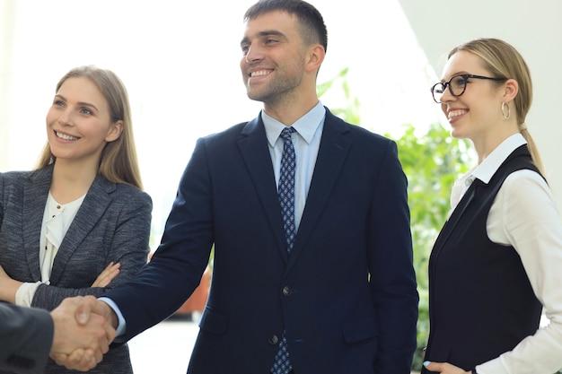 Gente de negocios dándose la mano, terminando una reunión.