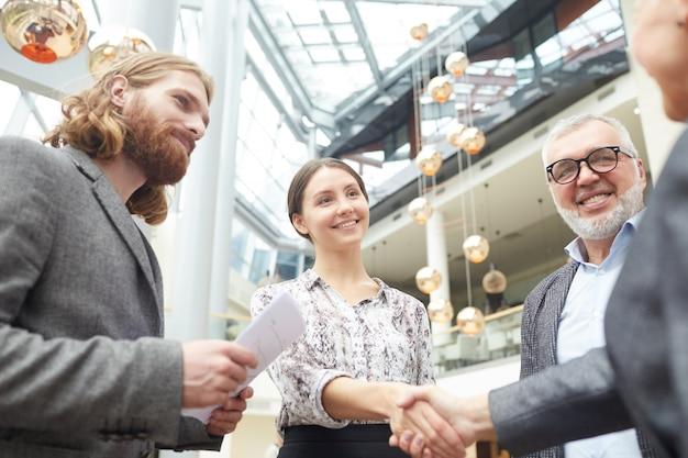 Gente de negocios dándose la mano en el vestíbulo