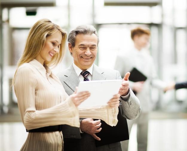 La gente de negocios discute el trabajo con una tableta digital