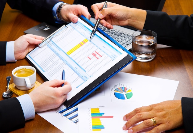 Gente de negocios discutiendo los cuadros y gráficos que muestran los resultados de su exitoso trabajo en equipo