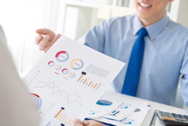 Gente de negocios discutiendo tabla de análisis financiero