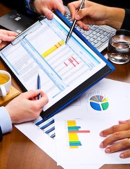 Gente de negocios discutiendo las tablas y gráficos que muestran los resultados de su exitoso trabajo en equipo