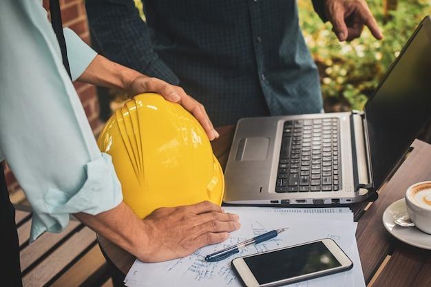 Gente de negocios dos personas que se encuentran proyecto de construcción en el cuaderno de la computadora en el escritorio, empresario capataz supervisor trabajador de computadora portátil de casco