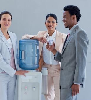 Gente de negocios con un enfriador de agua en la oficina