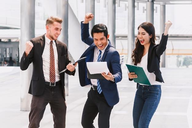 Gente de negocios exitosa celebrando con los brazos arriba