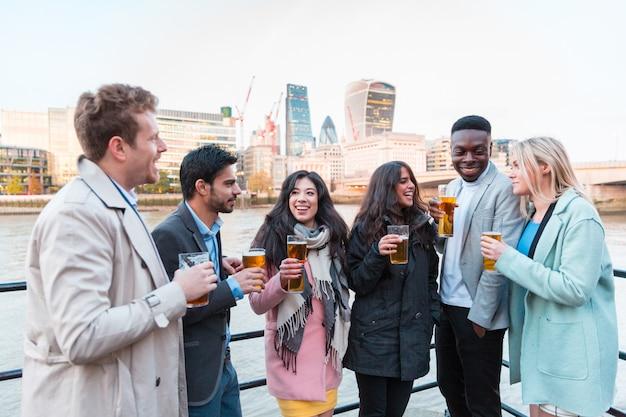 Gente de negocios feliz bebiendo cerveza después del trabajo en londres