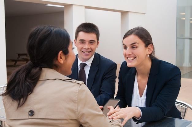 Gente de negocios feliz y cliente hablando en el escritorio al aire libre