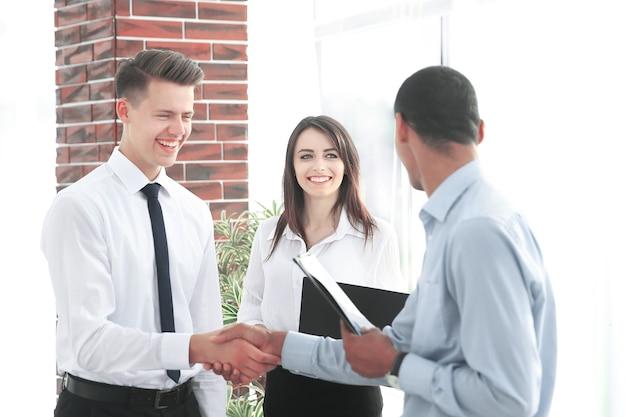 Gente de negocios feliz estrecharme la mano en la oficina