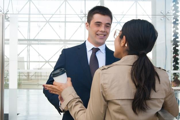 Gente de negocios feliz gesticulando y discutiendo ideas al aire libre