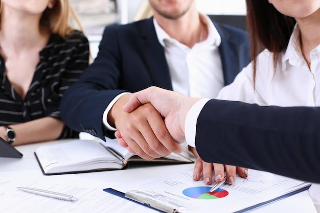 Gente de negocios del grupo se dan la mano como hola en primer plano de la oficina