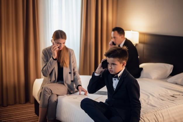 Gente de negocios en la habitación del hotel con su pequeño hijo