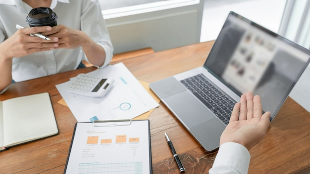 Gente de negocios hablando discutiendo con un compañero de trabajo planeando analizar tablas de datos de documentos financieros