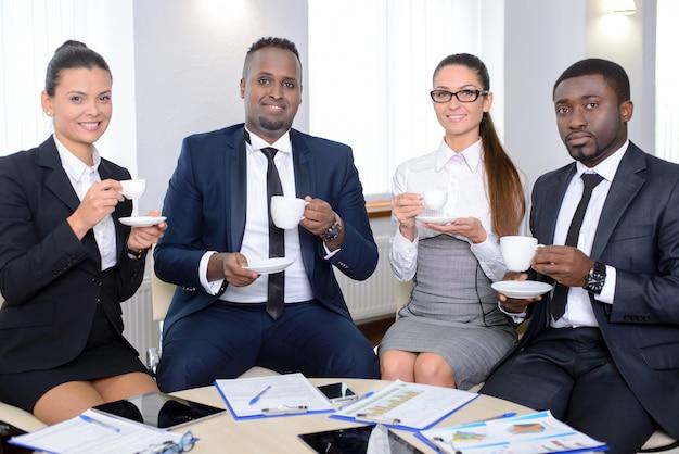 La gente de negocios se hizo un café en el trabajo.
