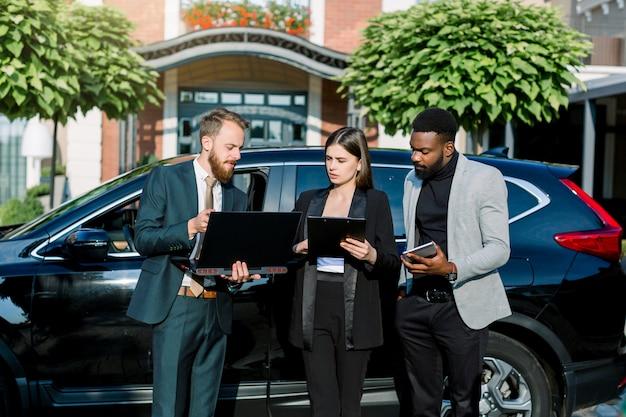 Gente de negocios, hombre africano, hombre y mujer caucásicos, trabajando con computadora portátil y tableta, mientras está de pie al aire libre de la oficina cerca del automóvil