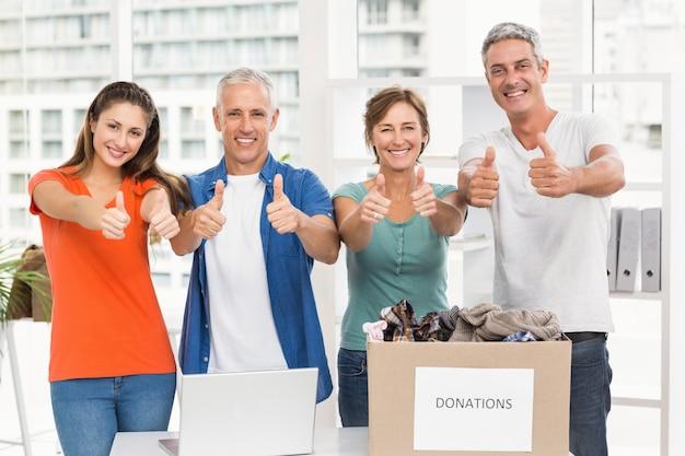 Gente de negocios informal donando y haciendo pulgares arriba