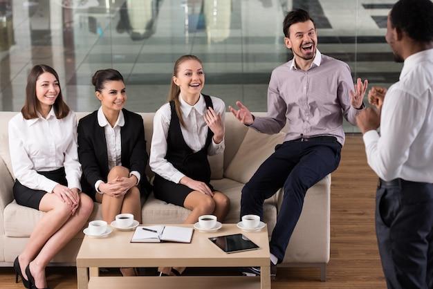 La gente de negocios está interactuando y tomando café.