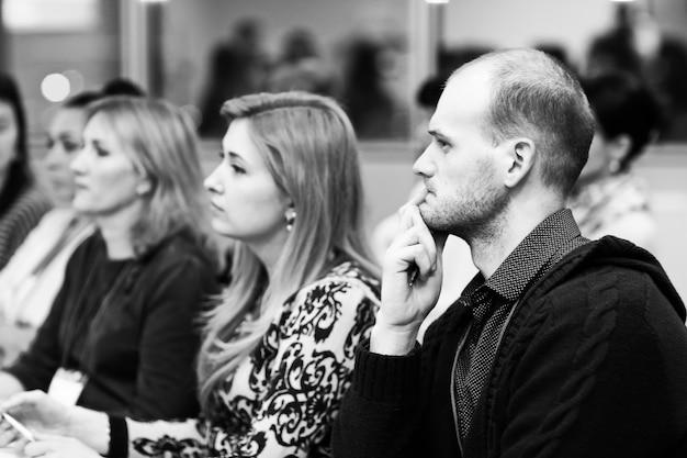 Gente de negocios interesada escuchando conferencias, sentados en el