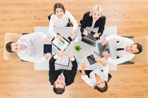 La gente de negocios levanta el pulgar en la mesa. vista desde arriba