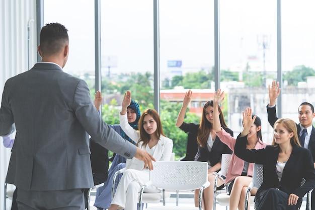 Gente de negocios levantando su mano en la votación de concfence de negocios