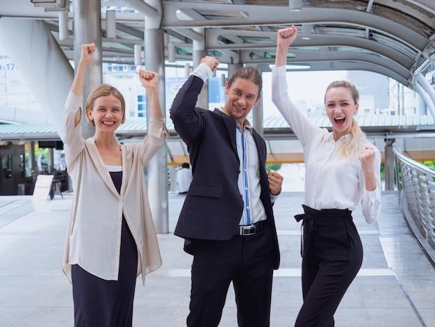 Gente de negocios logrando objetivos, equipo de negocios feliz celebrando la victoria en la ciudad