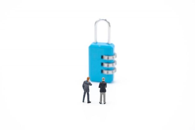 Gente de negocios en miniatura analiza la contraseña.