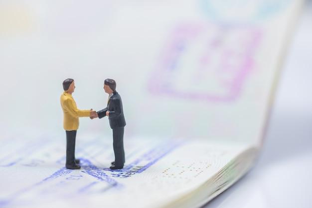 Gente de negocios en miniatura estrechándose la mano en el libro de pasaportes