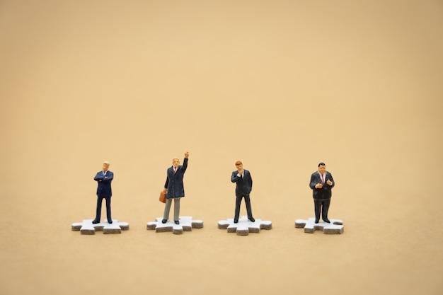 Gente de negocios en miniatura personas de pie en blanco jigsaw