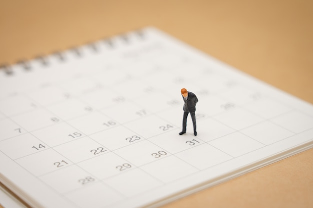 Gente de negocios en miniatura personas de pie en el calendario blanco
