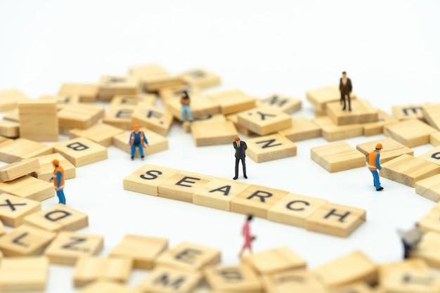 Gente de negocios en miniatura personas de pie con la palabra madera buscar. encontrar algo